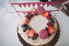 Children`s birthday cake with berries and macaroons royalty free stock photos