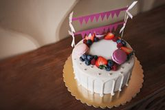 Children`s birthday cake. On the cake there are raspberry berries, blueberries and strawberries, purple and pink macaroons, decora royalty free stock photography