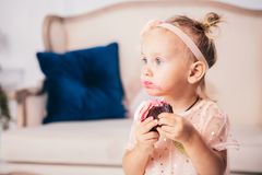 Children`s birthday. funny two-year-old Caucasian girl in pink dress standing to bedroom of house the background of couch and eat stock image