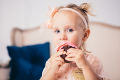 Children`s birthday. funny two-year-old Caucasian girl in pink dress standing to bedroom of house the background of couch and eat royalty free stock photography