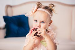 Children`s birthday. funny two-year-old Caucasian girl in pink dress standing to bedroom of house the background of couch and eat royalty free stock photo
