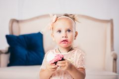 Children`s birthday. funny two-year-old Caucasian girl in pink dress standing to bedroom of house the background of couch and eat. Ing, holding cake dessert stock photo