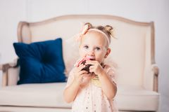 Children`s birthday. funny two-year-old Caucasian girl in pink dress standing to bedroom of house the background of couch and eat. Ing, holding cake dessert royalty free stock photos