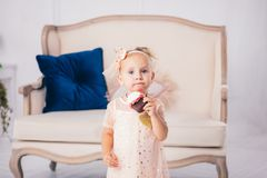 Children`s birthday. funny two-year-old Caucasian girl in pink dress standing to bedroom of house the background of couch and eat. Ing, holding cake dessert royalty free stock photography