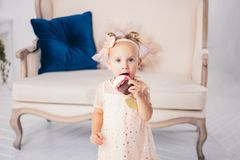 Children`s birthday. funny two-year-old Caucasian girl in pink dress standing to bedroom of house the background of couch and eat. Ing, holding cake dessert stock photography