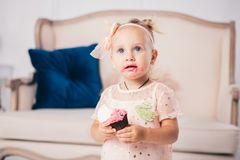 Children`s birthday. funny two-year-old Caucasian girl in pink dress standing to bedroom of house the background of couch and eat royalty free stock photos