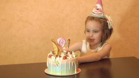Children`s birthday party. Little girl looking at the cake and licking. family celebration. Stock Photo