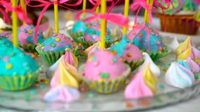 Children`s birthday party. Slow close-up motion of lollipops decorated with sweets. Children`s birthday party. Unicorn themed treats, against colorful background stock footage