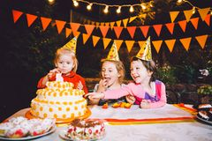 Children`s birthday party. Three cheerful children girls at the table eating cake with their hands and smearing their face. Fun a stock photo