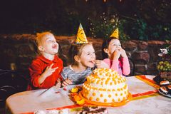 Children`s birthday party. Three cheerful children girls at the table eating cake with their hands and smearing their face. Fun a Royalty Free Stock Image
