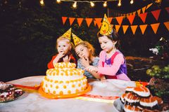 Children`s birthday party. Three cheerful children girls at the table eating cake with their hands and smearing their face. Fun a royalty free stock photos
