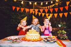 Children`s birthday party. Three cheerful children girls at the table eating cake with their hands and smearing their face. Fun a Royalty Free Stock Images