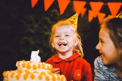 Children`s birthday party. Three cheerful children girls at the table eating cake with their hands and smearing their face. Fun a royalty free stock photography