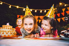 Children`s birthday party. Three cheerful children girls at the table eating cake with their hands and smearing their face. Fun a stock image
