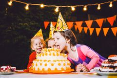 Children`s birthday party. Three cheerful children girls at the table eating cake with their hands and smearing their face. Fun a stock photos