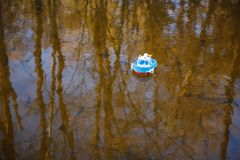 Children`s boat blue goes on the golden water stock images