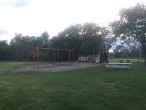 Children& x27; s boisko przy półmrokiem z huśtawkami, obruszeniem, trawą i pyknicznym stołem, Obraz Stock