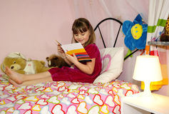 Children's book reading. Cute young girl reading a book Stock Images
