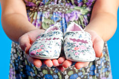 Children's bootees. The future mum holds on hands children's bootees Stock Photos