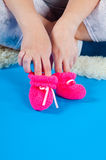 Children's bootees. The future mum plays with children's bootees on a blue background Stock Photography