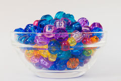 Children`s bright and colorful beads displayed in a simple glass bowl Royalty Free Stock Photography