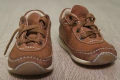 Children's brown shoes on the floor. Children's brown shoes with laces on the floor stock photos