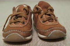 Children's brown shoes on the floor. Children's brown shoes with laces on the floor stock photography
