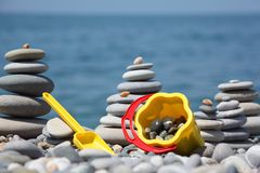 Children's bucket with scoop and stone stacks Stock Photo