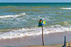 Children`s cap hanging on a stick inserted on the beach, on the sea. stock photo