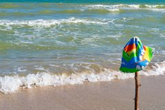 Children`s cap hanging on a stick inserted on the beach, on the sea. royalty free stock photography