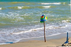 Children`s cap hanging on a stick inserted on the beach, on the sea. stock images