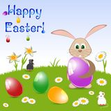 Children's card for Easter with painted eggs and rabbit on floral meadow Stock Photography