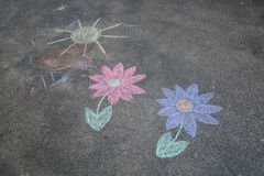 Children's chalk drawing. Child's drawing with chalk on asphalt. Sun and flowers Stock Image