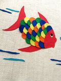 Children's chore, cloth fish. Colorful fish made for children. This is a chore that is done at school with pieces of colored cloth. The fabric is glued onto stock photography