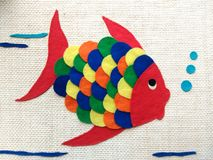 Children's chore, cloth fish. Colorful fish made for children. This is a chore that is done at school with pieces of colored cloth. The fabric is glued onto royalty free stock images