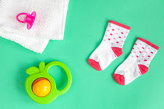 Children`s clothes and baby booties on green background. Top view Stock Photo