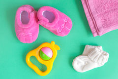 Children`s clothes and baby booties on green background. Top view Royalty Free Stock Photos