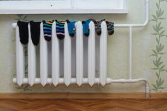 Children`s clothes dry on the radiator. Children`s clothes such as socks, shirt, shorts, tights dry on the radiator at home Royalty Free Stock Photos