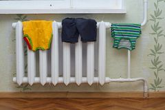 Children`s clothes dry on the radiator. Children`s clothes such as socks, shirt, shorts, tights dry on the radiator at home Royalty Free Stock Images