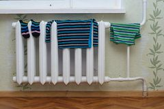 Children`s clothes dry on the radiator. Children`s clothes such as socks, shirt, shorts, tights dry on the radiator at home Stock Photos