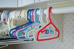 Children's Clothes Hangers. Empty kids clothes hangers hanging on a bar in a laundry room Stock Photography