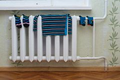 Children`s clothes dry on the radiator. Children`s clothes such as socks, shirt, shorts, tights dry on the radiator at home Stock Photography