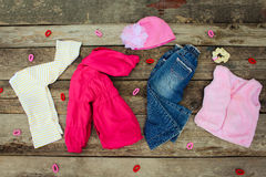 Children's clothing and accessories: jeans, jacket, hat, hair clips and warm vest Stock Photo