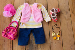 Children's clothing and accessories: vest, jeans, jacket, shoes, hat and handbag Stock Photos