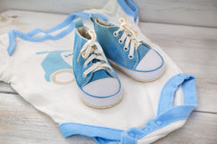 Children`s clothing for boys and shoes on a wooden background Stock Images