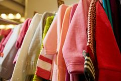 Children`s clothing of different colors hanging on hangers in the  store Stock Photos