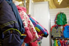 Children`s clothing of different colors hanging on hangers in the  store Royalty Free Stock Image