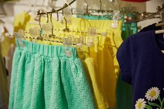 Children`s clothing of different colors hanging on hangers in the  store Stock Photo