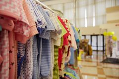 Children`s clothing of different colors hanging on hangers in the  store Royalty Free Stock Photo