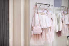 Children`s clothing for girls. Fancy dresses in the store. Dressing room Stock Photos